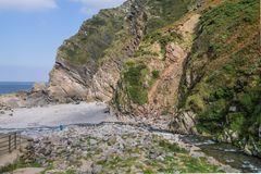 Side view of the cliffs at Heddon`s Mouth in north Devon. E view of the cliffs at Heddon`s Mouth in north Devon, with tiny figures dwarfed by the towering cliffs stock images