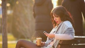Attractive cute brunette girl sits on bench in city park and drinks hot coffee from which there is steam and writes in phone. Side view, close-up attractive cute stock footage