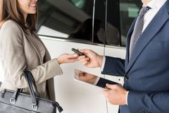 Car Salesman Giving Keys to Client. Side view  close up of car salesman giving keys to client standing next to white luxury car, copy space Stock Photography