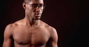 Side view close up cropped portrait of strong nacked Afro male in glasses royalty free stock photos