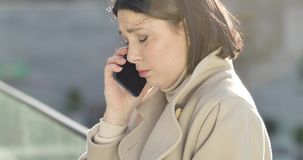 Side view close-up face of upset Caucasian woman talking on the phone and crying. Pretty stressed businesswoman having