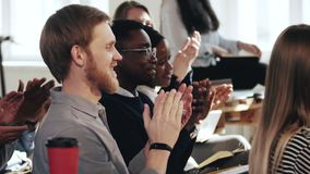 Side view close-up happy smiling young multiethnic audience clapping to speaker at modern office training seminar event.