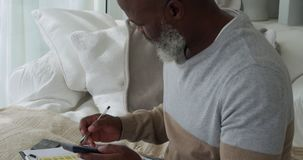 Mature man at home. Side view close up of a mature mixed race man using a calculator and writing on a clipboard at home stock footage