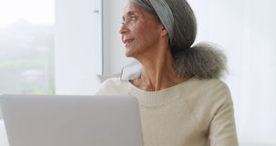 Mature woman at home. Side view close up of a mature mixed race woman using a laptop computer and looking out of the window stock footage