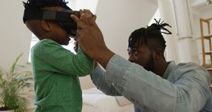 Father and son at home using VR