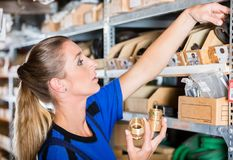 Happy worker holding a high-quality pipe fitting accessory in a sanitary shop. Side view close-up portrait of a happy blue-collar worker holding a high-quality royalty free stock images