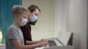 A side view close up shooting of a teacher and her student both having medical masks on their faces and having a music