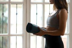 Female wearing sportswear standing near window holding yoga mat royalty free stock images