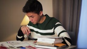 Side view close-up of tired Asian college student doing homework at home. Young handsome boy reading and writing in