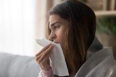 Side view close up woman holding paper tissue sneezing stock image
