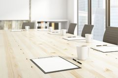 Boardroom concept. Side view and close up of wooden conference table with clipboards and coffee cups. Boardroom concept. 3D Rendering Royalty Free Stock Photo