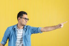 Side-view, close up of young Asian handsome bearded man, wearing eyeglasses, in denim shirt, pointing playfully to his left side,. With yellow stripe wall royalty free stock photography