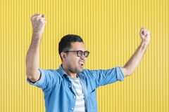 Side-view, close up of young Asian handsome bearded man, wearing eyeglasses, in denim shirt, pointing playfully to his left side,. With yellow stripe wall stock photos