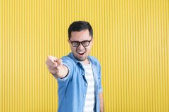 Side-view, close up of young Asian handsome bearded man, wearing eyeglasses, in denim shirt, pointing playfully to his left side, stock image