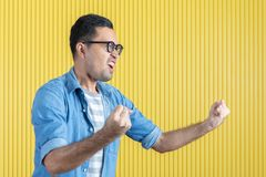 Side-view, close up of young Asian handsome bearded man, wearing eyeglasses, in denim shirt, pointing playfully to his left side,. With yellow stripe wall stock photo