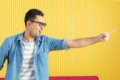Side-view, close up of young Asian handsome bearded man, wearing eyeglasses, in denim shirt, pointing playfully to his left side,. With yellow stripe wall stock image