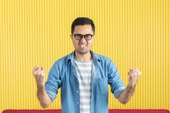 Side-view, close up of young Asian handsome bearded man, wearing eyeglasses, in denim shirt, pointing playfully to his left side, royalty free stock images