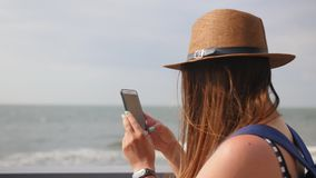 Side view, close-up, young girl in a hat walks at promenade in summer, takes a photo on her smartphone, enjoys a walk stock video