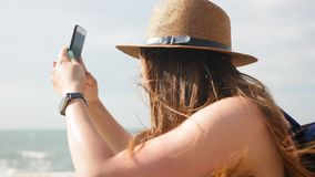 Side view, close-up, young girl in a hat walks at promenade in summer, takes a photo on her smartphone, enjoys a walk.  stock video footage