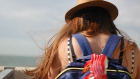 Side view, close-up, young girl in a hat walks at promenade in summer, takes a photo on her smartphone, enjoys a walk.  stock footage