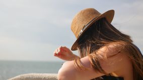 Side view, close-up, young girl in a hat walks at promenade in summer, takes a photo on her smartphone, enjoys a walk.  stock video