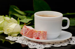 Side view of a coffee cup with milk close-up, oriental sweets. smartphone, white roses on a black background Royalty Free Stock Images