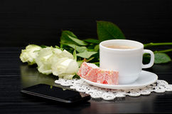 Side view of a coffee cup with milk, oriental sweets. smartphone, white roses. Stock Images