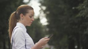 Side view of a college girl text messaging mobile phone in the park. closeup stock video
