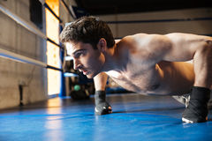 Side view of concentrated boxer doing push ups. Side view of a concentrated boxer with naked torso doing push ups on boxing ring stock photos