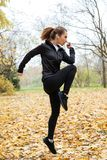 Side view of a concentrated fitness girl listening to music. While working out outdoors Stock Images