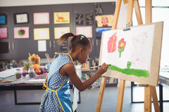 Side view of concentrated girl painting on canvas. In classroom stock images