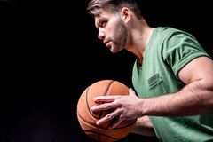 Side view of concentrated man holding basketball ball Stock Images