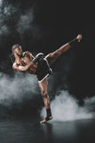Side view of concentrated muay thai fighter practicing kick  on black Royalty Free Stock Images