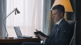 Adult businessman using phone and laptop. Side view of confident adult man in suit sitting at table in hotel room working on laptop and having business call stock video