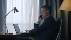 Adult businessman using phone and laptop. Side view of confident adult man in suit sitting at table in hotel room working on laptop and having business call stock video footage