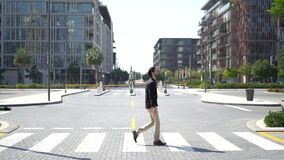 Side view of confident businessman passing crosswalk in modern district of megalopolis