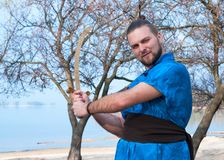 Side view of confident handsome man in blue kimono with belt, bun and sticks on head holding sword royalty free stock photo