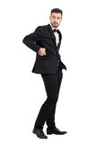 Side view of confident handsome man in tuxedo putting cellphone in coat pocket turning behind Stock Photo