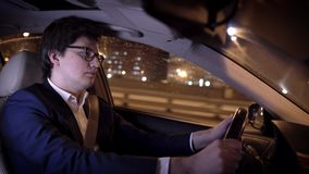 Young businessman in glasses driving a car in a night city. Side view of a confident and handsome young businessman driving his car in a night city. Concept of stock footage