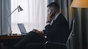 Stylish businessman using phone and laptop. Side view of confident man in suit sitting at table in hotel room working on laptop and having business call stock footage
