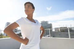 Side view of confident woman standing for breast cancer awareness. E view of confident woman standing for breast cancer awareness against urban background stock photos