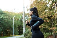 Side view of a confident young fitness woman jogging royalty free stock images