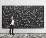 Side view of a confident young man who stands in front of black chalkboard which is full of math formulas. A concept of Analyst at Stock Images