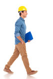 Side view of a  construction engineering student walking with cl. Side view of a young construction engineering student walking with clipboard  on white Royalty Free Stock Photography