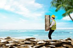 Side view of construction workers carrying coin stacks. Summer saving concept royalty free stock photos