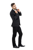 Side view of cool elegant young male model adjusting bow tie looking at camera Stock Photography
