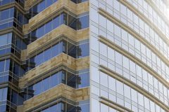 Side view of a corporate building façade made of glass windows and cream yellowish tiles. stock photo