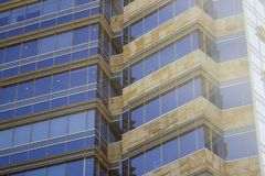 Side view of a corporate building façade made of glass windows and cream yellowish tiles. Low angle shot. The sun gleams through the right stock photography