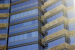 Side view of a corporate building façade made of glass windows and cream yellowish tiles. Low angle shot. The sun gleams through the right stock photos