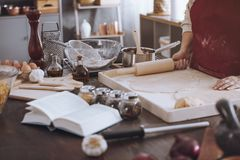 Cookbook and bowls on countertop. Side view of countertop with cookbook, bowls and kitchen tools during preparation of pizza royalty free stock photo